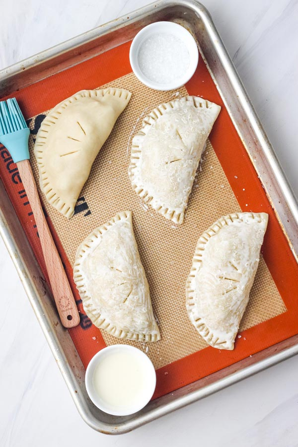 Hand pies brushed with cream on a quarter sheet pan lined with a silicone baking mat.