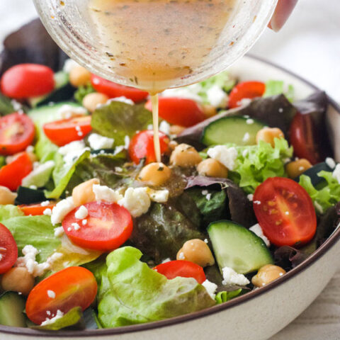 Hand pouring dressing from a mason jar onto a bowl of salad.