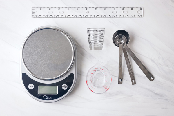 Digital scale, mini liquid measuring cups, small measuring spoons, and a plastic ruler.