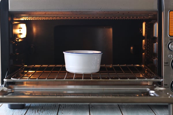 Oven-safe ramekin warming ingredients in a toaster oven.