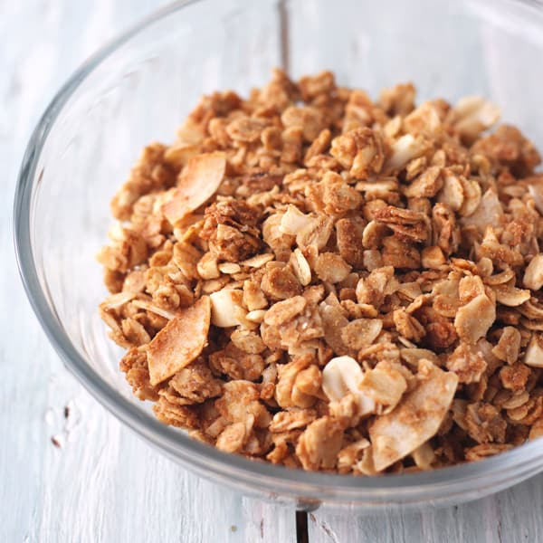 Flaky stirred granola in a glass bowl.