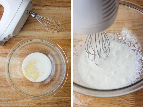 A glass bowl with cream next to a mixer and a bowl of cream whipped with bubbles.
