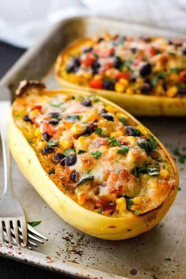 Two spaghetti squash boats on a metal sheet pan with two forks.