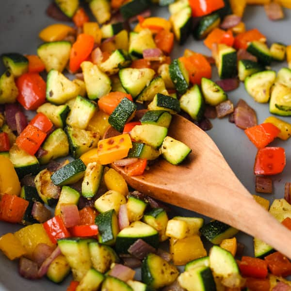 Skillet with vegetables on a wooden spoon.