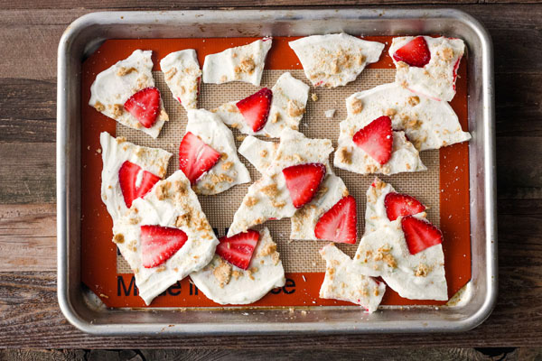 Strawberry Lime Yogurt Bark broken into pieces on a baking sheet.