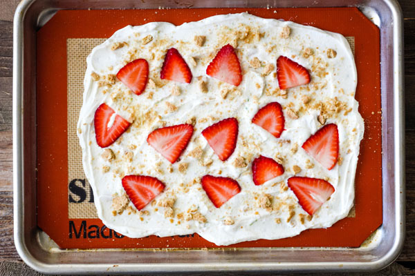 Yogurt spread onto a silicone baking mat topped with strawberries and graham cracker.