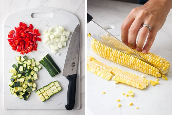 Slicing corn of cob on a cutting board and piles of chopped red pepper, zucchini, and onion.