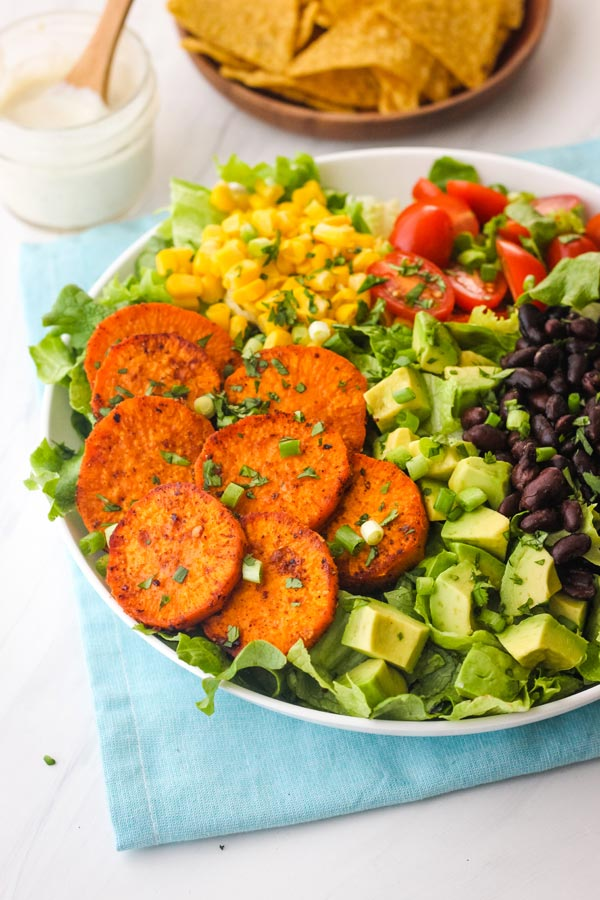 Bowl of salad with sweet potato slices, avocado, black beans, and corn.