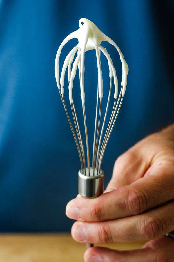 A man's hand holding a whisk covered in whipped cream with the tip folding over.