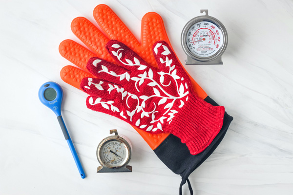 Oven thermometers, orange and red oven gloves, and an instant read thermometer.