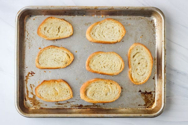 Golden toasted bread slices on a sheet pan.