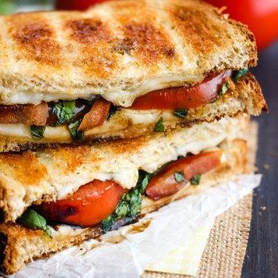 Toasted Caprese Sandwich on a piece of parchment.