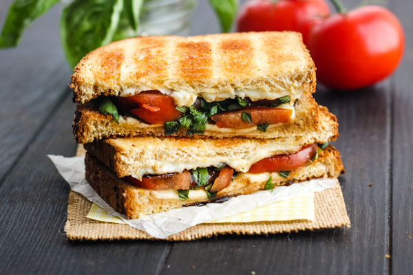 Toasted Caprese Sandwich on a wooden table.