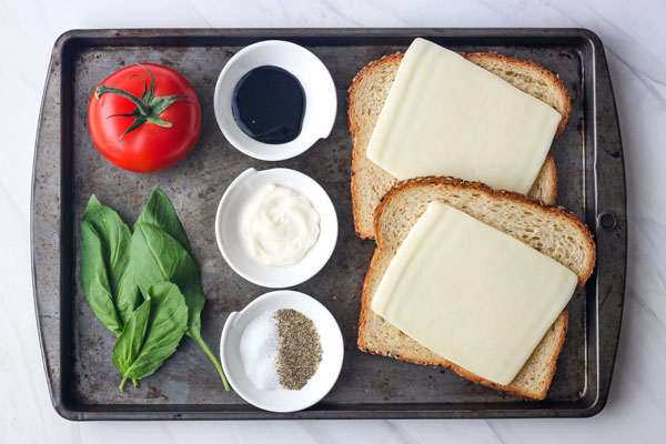 Toasted Caprese Sandwich ingredients on a baking sheet.
