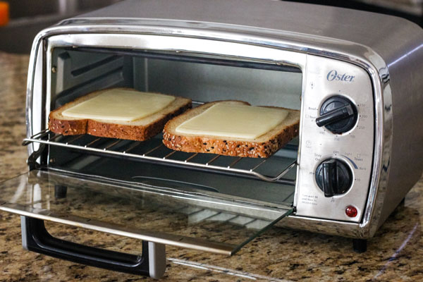 Toasted bread slices with cheese inside a toaster oven.