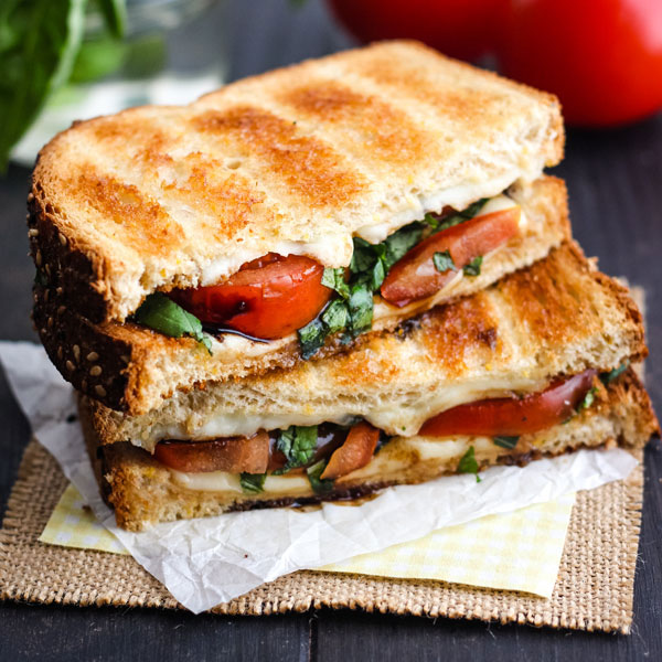 Toasted Caprese Sandwich sliced in half on a piece of parchment.