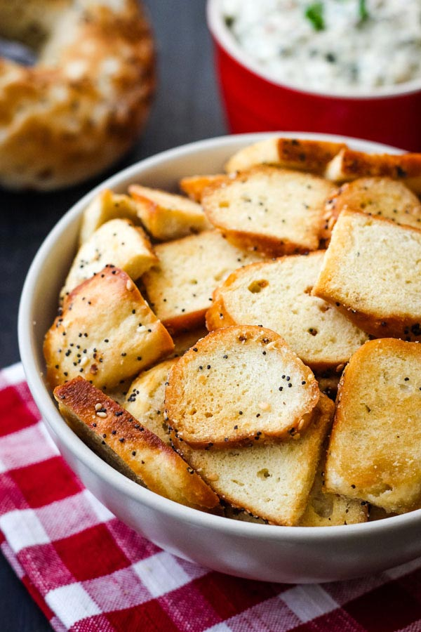 Toaster oven bagel chips in a bowl on a red checkered napkin.
