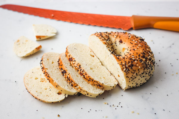 Everything bagel sliced on a cutting board with an orange knife.