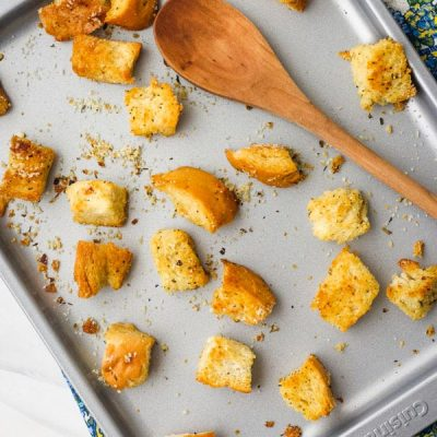 Baked croutons a small baking sheet with a wooden spoon.