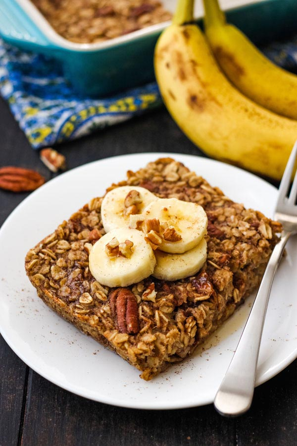 Baked oatmeal topped with banana slices and pecans on a white plate.
