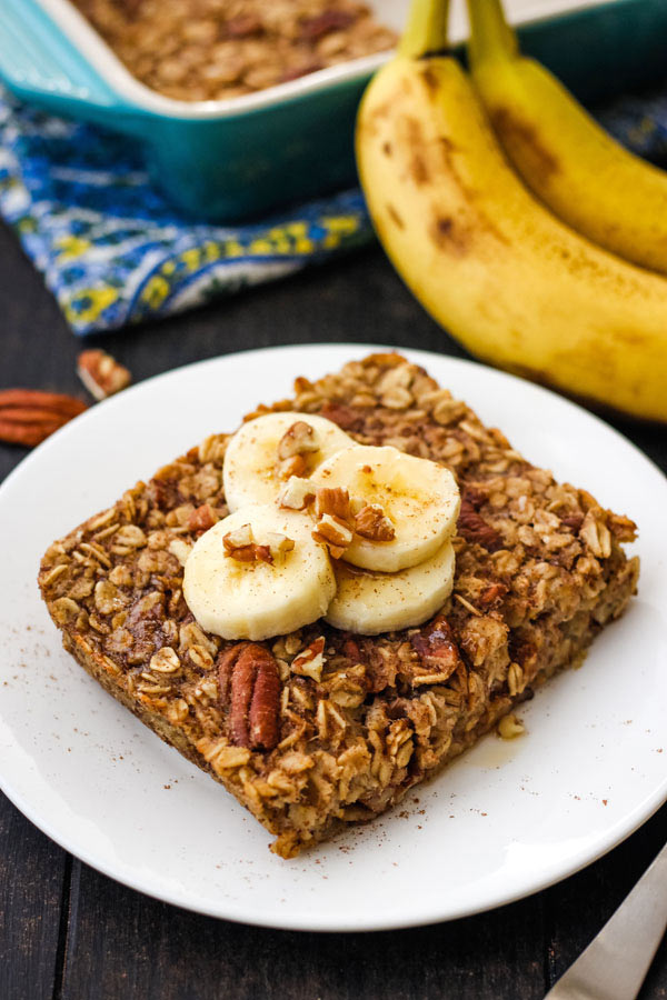 Baked oatmeal square topped with banana slices on a white plate.