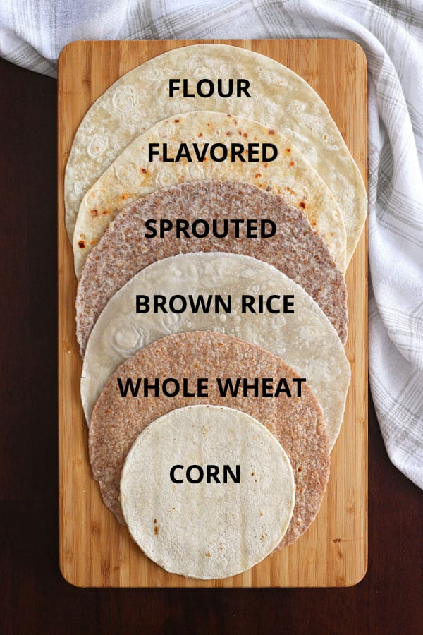 A variety of tortillas including brown rice, sprouted grain and flour tortillas on a cutting board.