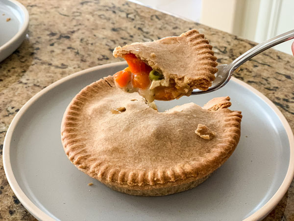 Fork holding a piece of pot pie over a blue plate.