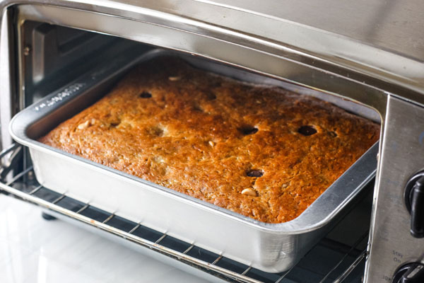 A small cake pan of baked bread inside a toaster oven.