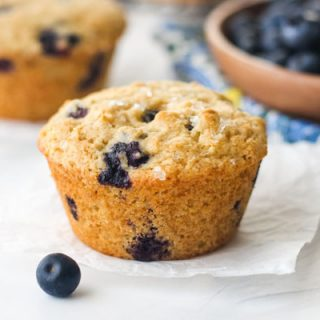 Blueberry Muffins on a table with a bowl of fresh blueberries.