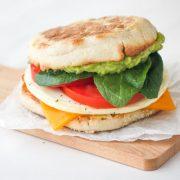 Breakfast sandwich on a small wooden cutting board.