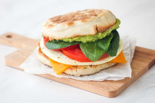 Breakfast sandwich on a small wooden cutting board.