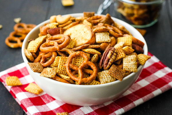 Snack mix in a white bowl on a red checkered napkin.