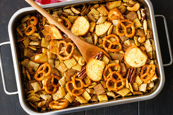 Snack mix in a small roasting pan with a wooden spoon.