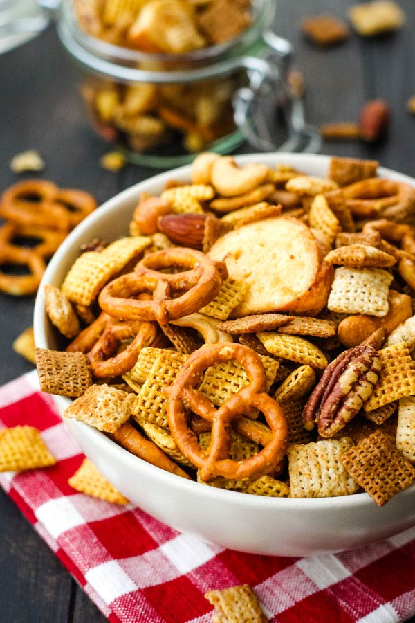 Chex mix in a white bowl on a red checkered napkin.