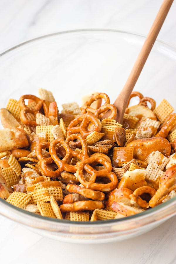 Chex mix ingredients in a glass bowl with a wooden spoon.