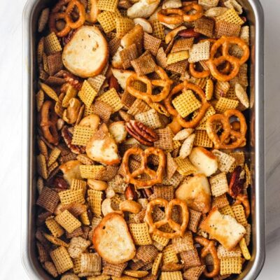 Toaster oven Chex mix in a small roasting pan.
