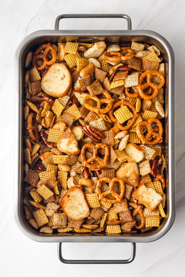 Baked Chex mix in a small roasting pan.