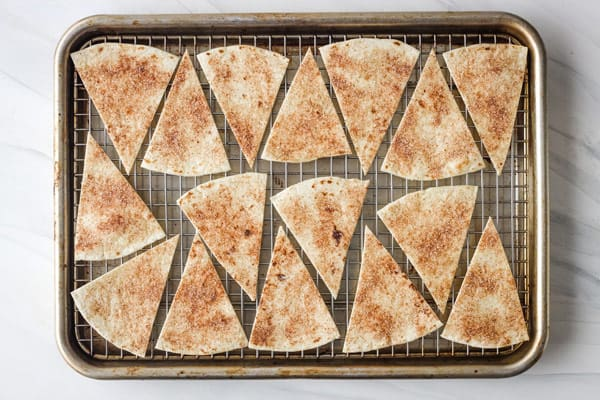 Unbaked chips on a cooking rack inside a pan.