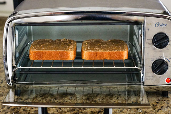 Two slices of bread on a rack inside a toaster oven.