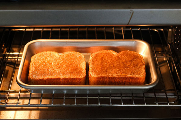 Bread slices on a baking sheet inside a countertop oven.