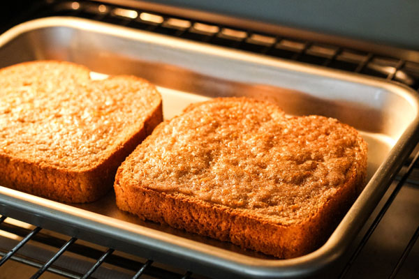 Sugar broiling on two slices of bread in a countertop oven.