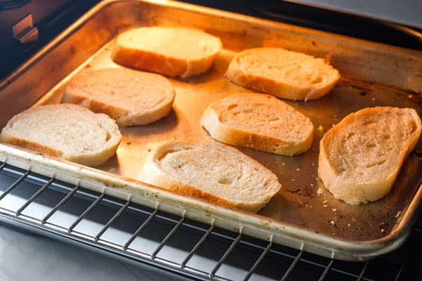Sheet pan with bread slices inside a toaster oven.
