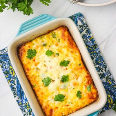 A small egg casserole in a blue baking dish on a white table.