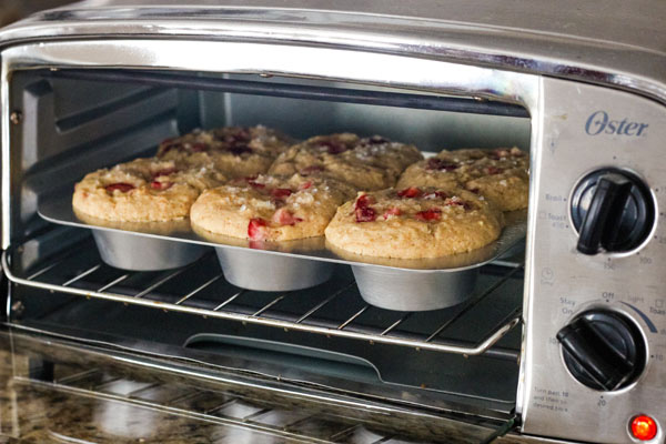 A pan of baked muffins inside a toaster oven.