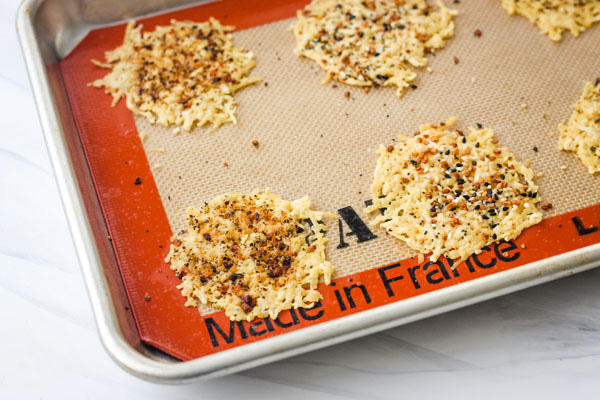 Baked parmesan crisps on a lined sheet pan.