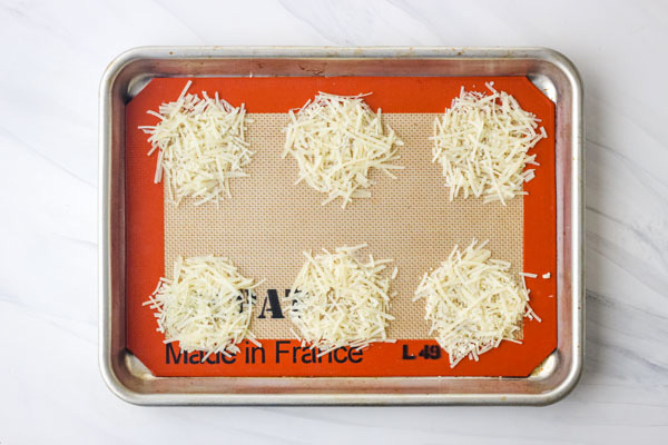 Piles of parmesan cheese on a silpat lined pan.