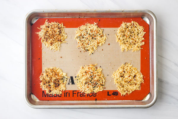 Parmesan baked crisps on a silicone baking mat lined pan.