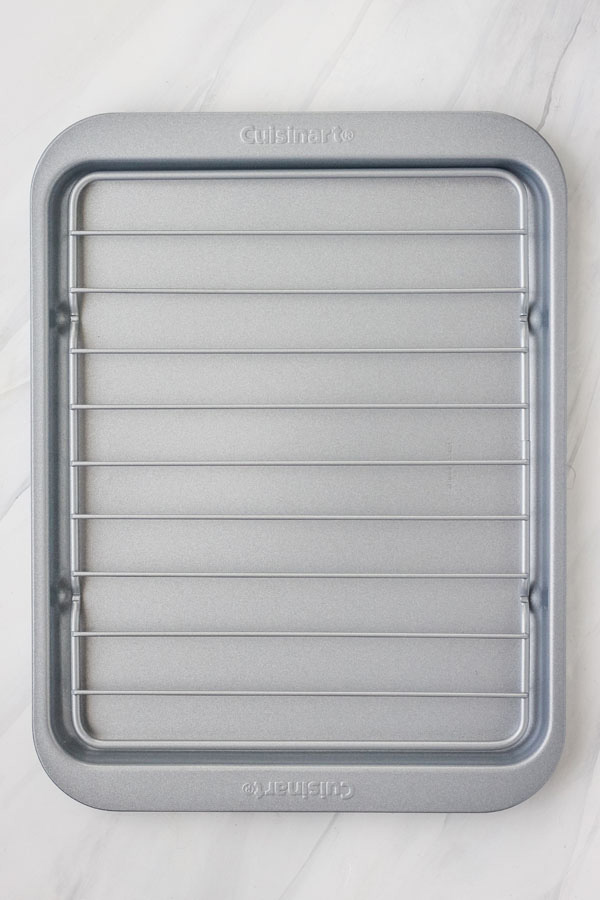 Metal toaster oven sheet pan with broiling rack on a white background.