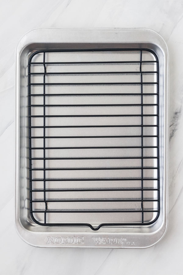 Nordic Ware Compact Oven Pan and Rack on a marble background.