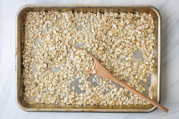 Toasted old fashioned oats in a rimmed sheet pan.